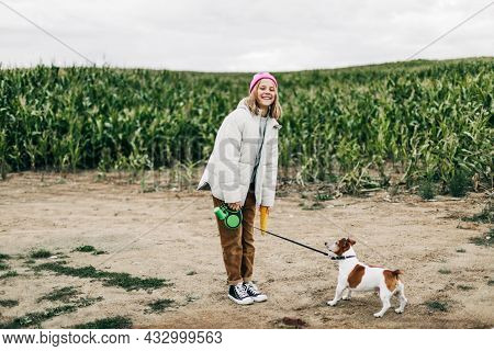 Cheerful Teenage Girl Playing In The Field With Her Dog Jack Russell Terrier On The Background Of A