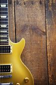 Vintage Gold top guitar on old wood surface. poster