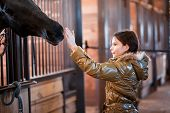 Teenage girl stroking horse while it pokes its head poster