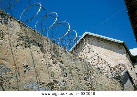 razor wire attached to the top of a concrete wall in fremantle prison in australia. poster