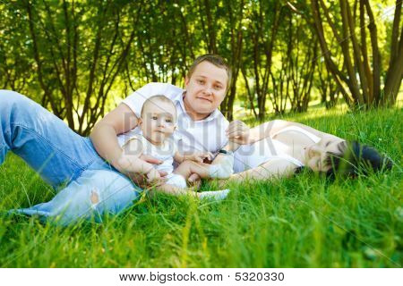 Mother, Father And Baby In Park