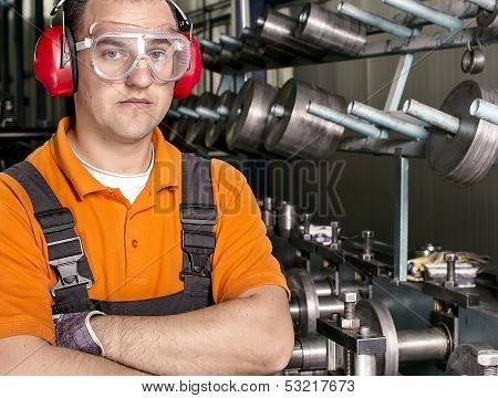 worker with antiphons and protection glasses in front of production machine poster