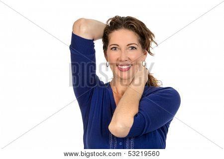 Glamurous middle aged woman smiles to the camera, whilst pushing her hair back from her face