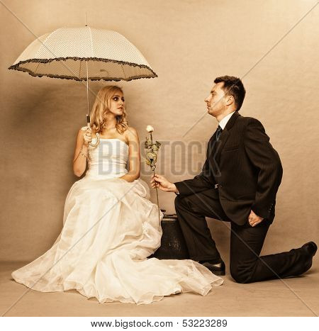 Wedding day. Portrait of romantic married couple blonde bride with umbrella and enamored groom giving a rose to girl. poster