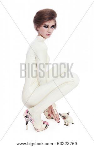 Model in beige latex catsuit with kitten over white background