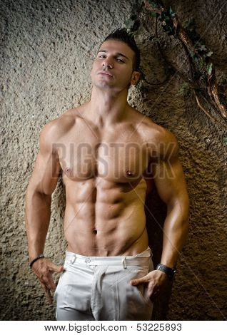 Handsome muscular man shirtless wearing white pants in front of concrete wall poster