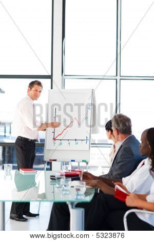 Young Businessman Reporting To Sales Figures To His Colleagues