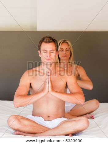 Young Couple On Buddha Position On Bed