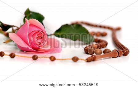 Muslim Rosary And Pink Rose On A White Background