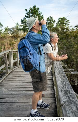 Senior Couple Hiking And Birdwatching On Old Wooden Foot Bridge
