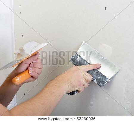 repairman works with plasterboard, plastering dry-stone wall, home improvement