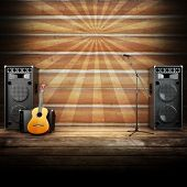 Country music stage or singing background, microphone, guitar and speakers with wood flooring and sunburst background. Advertising concept with room for text or copy space poster