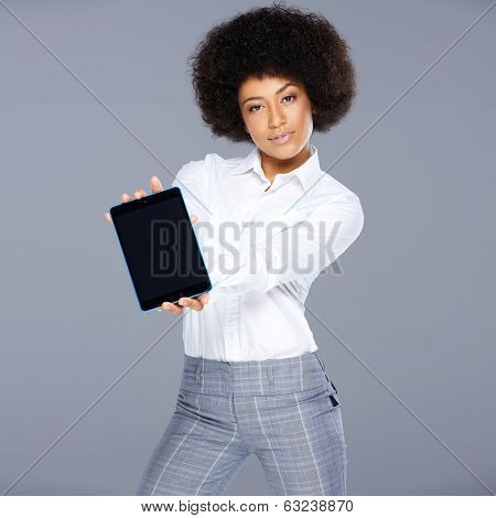 Stylish trendy beautiful African American woman showing a tablet computer holding the blank screen towards the viewer