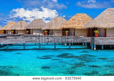 Luxury beach resort on Maldives, many cute bungalows standing on transparent water, Indian ocean, romantic place for honeymoon, summer vacation concept poster