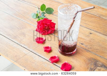 Red Rose And Cold Pomegranate Drink On Wood Table