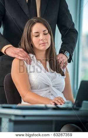 Business woman getting a massage from colleague in office
