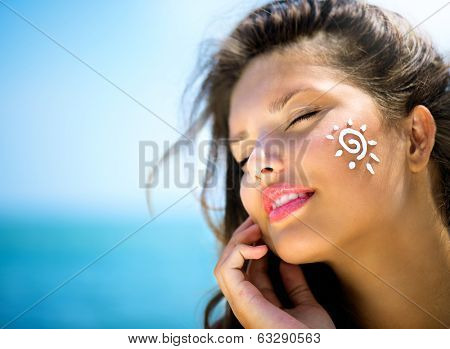 Suntan Lotion Woman Applying Sunscreen Solar Cream. Beautiful happy cute Girl applying Sun Tan Cream on her Face over ocean background. Sun Tanning. Skin care and Protection. Vacation