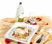restaurant table with meat with vegetables and glass for wine and bottle poster