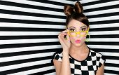Attractive surprised young woman wearing glasses on checkered background, beauty and fashion concept  poster