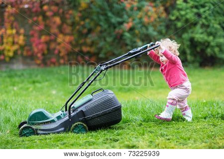 Cute Curly Baby Girl In Rain Boots Playing With A Big Green Lawn Mower In The Garden