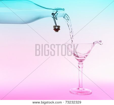 Clear Water Pour Out Of Bottle Splash Into Glass With Pink And Blue Back Lighting