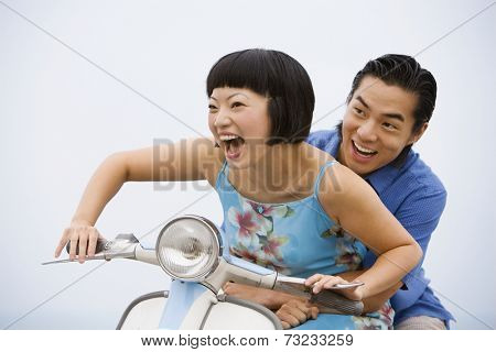 Asian couple riding motor scooter