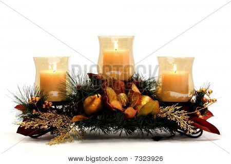 Three flaming candles on a centerpiece of pine and gold foliage. Isolated on white. poster