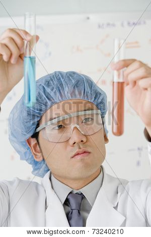 Asian male scientist comparing vials