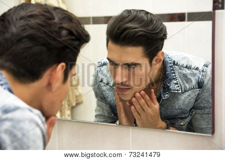Man Examining Face In Reflection Of Mirror