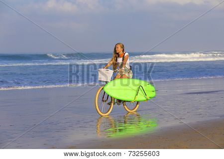 Young girl with surfboard and bicycle on the beach. poster