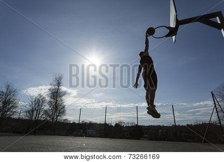 Basketball player silhouette slam dunking