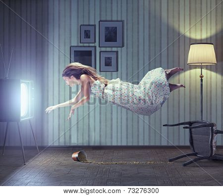 Young beautiful woman flying to tv screen in vintage interior. Creative concept