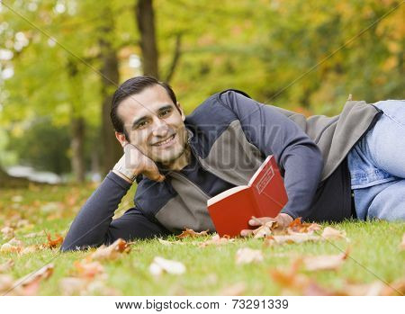 Hispanic man reading in grass