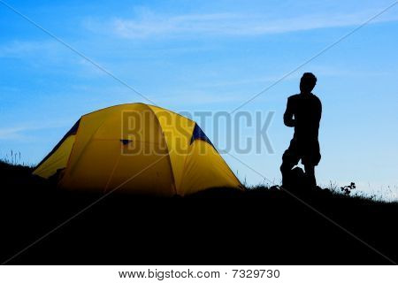 The dark outline of a hiker against the morning sky while the sun pierces the semi-transparent tent making it glow.