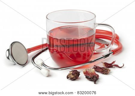 Cup of hibiscus tea and stethoscope on white background