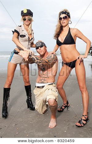 Two Female Models Standing On The Beach Arrest A Guy With Tattoos