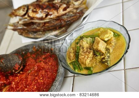 Indonesian local meal consisting sayur lodeh / vegetables with coconut milk soup and fried fish plus sambal / chili paste from Indonesia poster