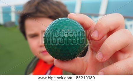 Little kid holds golf ball during a friendly match