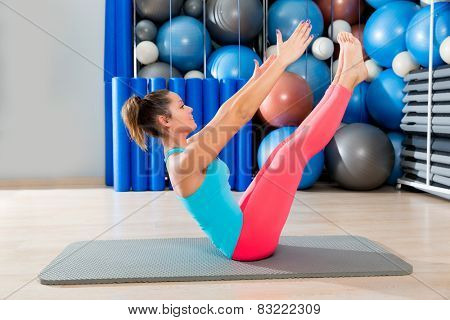 Pilates Teaser exercise woman on mat gym indoor and swiss balls background poster