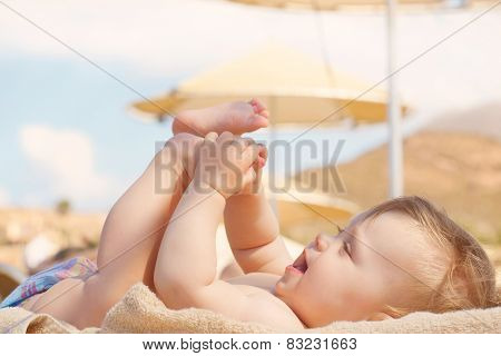 Happy Baby On Beach Lying On Lounger