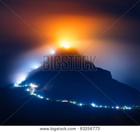 Mountain Adam's Peak (Sri Pada) covered by thick fog highlighted by illumination of the temple and lamps along the way to top. Sri Lanka