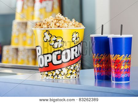 Popcorn bucket with cold drinks on concession counter at cinema