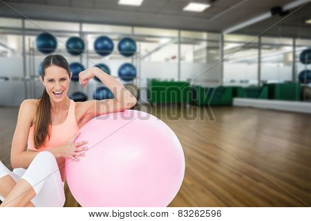 Cheerful fit woman flexing muscles by fitness ball against large empty fitness studio with shelf of exercise balls