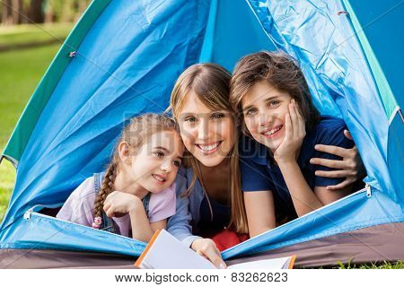 Portrait of happy children with mother holding book in tent at park