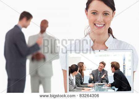 Happy team laughing together at a meeting against tradeswoman showing laptop with colleagues behind her