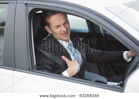 Businessman suffering from heartache in his car