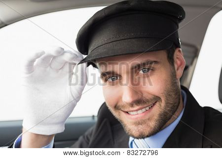Handsome chauffeur smiling at camera in the car