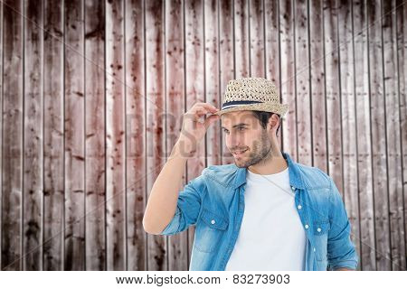 Handsome hipster wearing a trilby against wooden planks