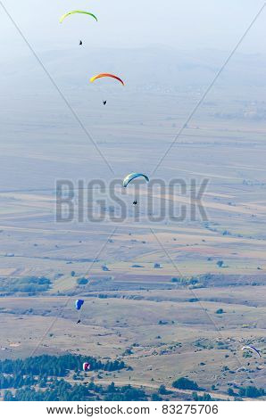Paragliding above the fields and hills, extreme sport
