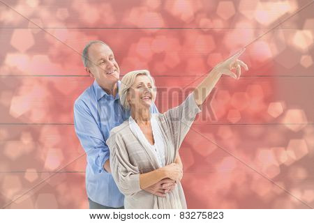 Happy mature couple embracing and looking against light glowing dots design pattern